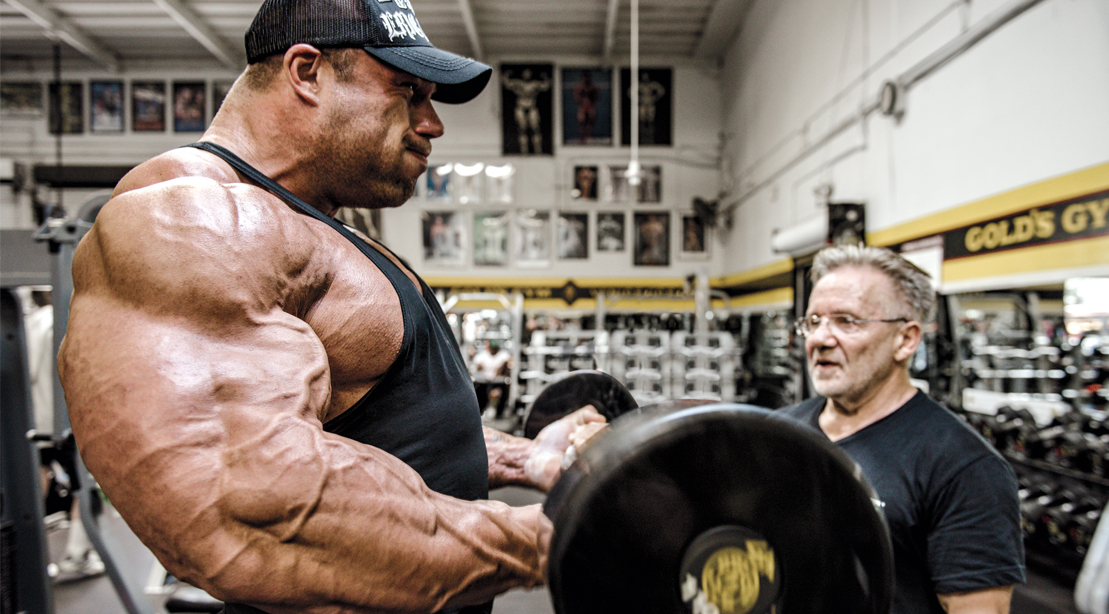 Professional bodybuilder working out his arms with one of the best arm exercises the standing barbell bicep curl