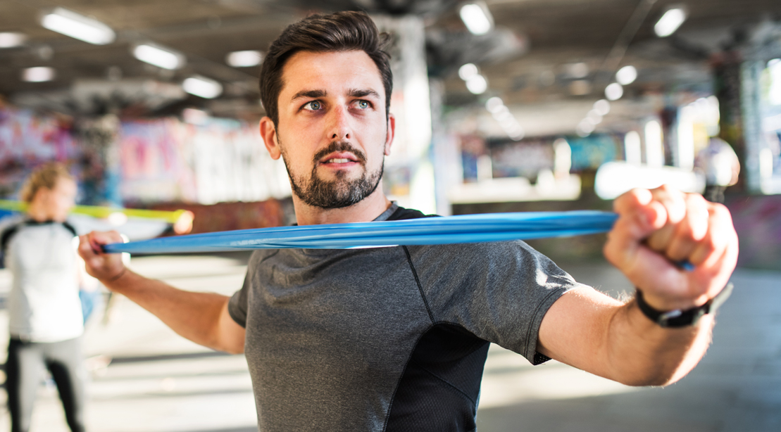 Fit man working out with a band workout in the gym