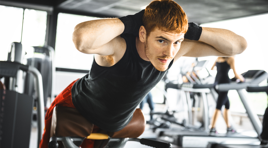 Muscular young man working out with core exercises and performing a back extension