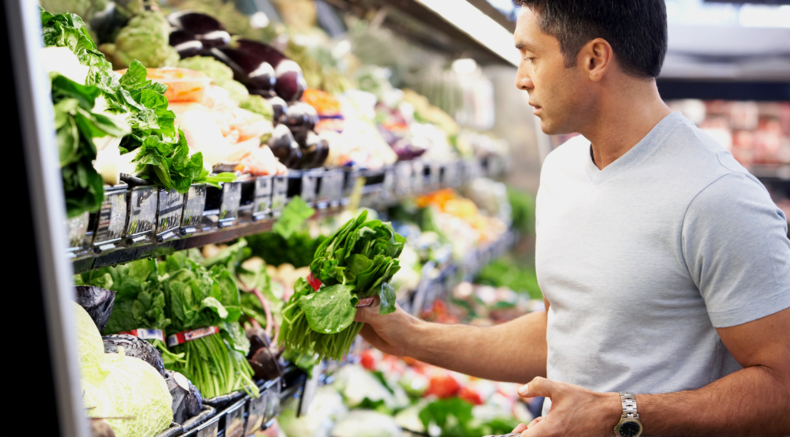 Man grocery shopping and looking at spinach in the vegetable section