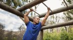 Strong muscular man building his biceps and arms with monkey bar exercise