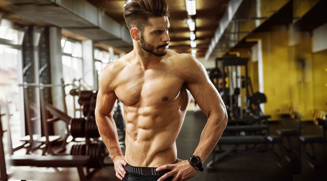 Muscular man with ab muscles standing in a gym after doing abs exercises