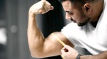Strong muscular man measuring his bicep growth using a measuring tape