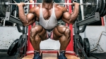 Bodybuilder AKIM squatting and working out his lower body with a leg exercise