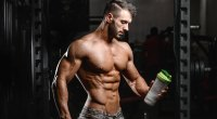 Bodybuilder looking at a shaker filled with a protein shake