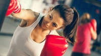 Female-Boxer-Throwing-Cross-To-A-Heavy-Bag