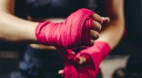 Female-Boxer-wrapping-her-hands-for-a-boxer