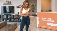 Female-Fitness-Model-On-Her-Smart-Phone-With-Trifecta-Box-On-Kitchen-Table