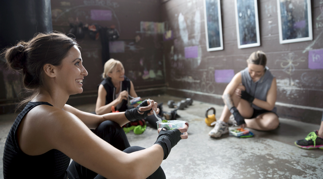 Fit girl eating a salad with a group of fitness enthusiasts in the gym