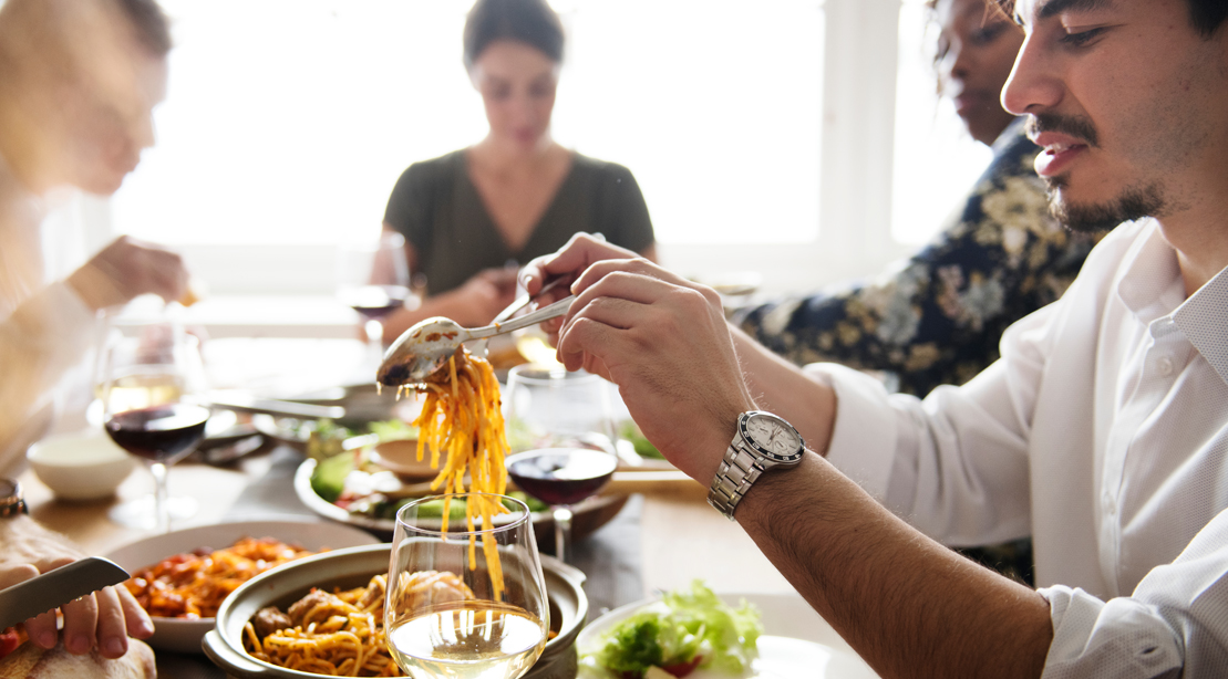 Group of friends eating a high carb meal serving pasta