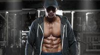 Muscular fitness model showing his abs and chest muscle while wearing a hoodie and hat