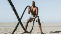 Muscular man working out with battle ropes on the beach