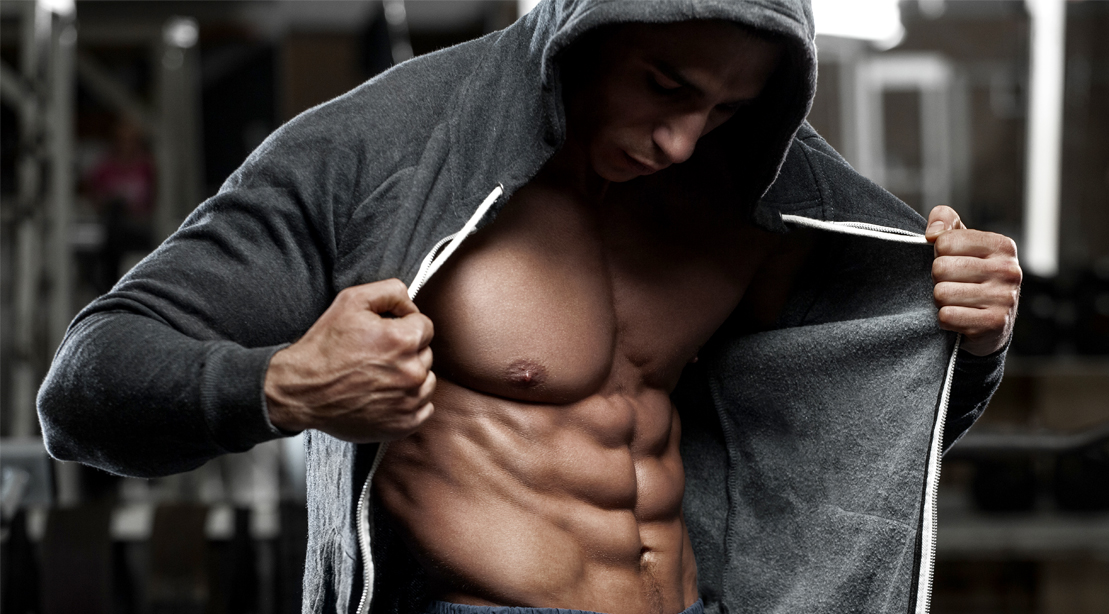 Bodybuilder opening his hoodie to show his six pack abs and washboard stomach to reveal your lower abs