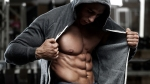 Bodybuilder opening his hoodie to show his six pack and washboard abs