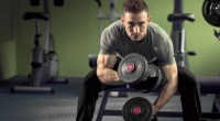 Guy-Sitting-On-Bench-Lifting-Dumbbells