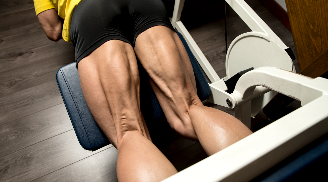 Muscular legs doing a hamstring workout by doing leg curl exercise