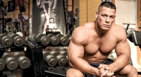 Wrestler and movie star John Cena sitting and resting on a bench in a gym