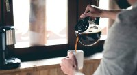 Man pours a pot of coffee into his morning coffee cup