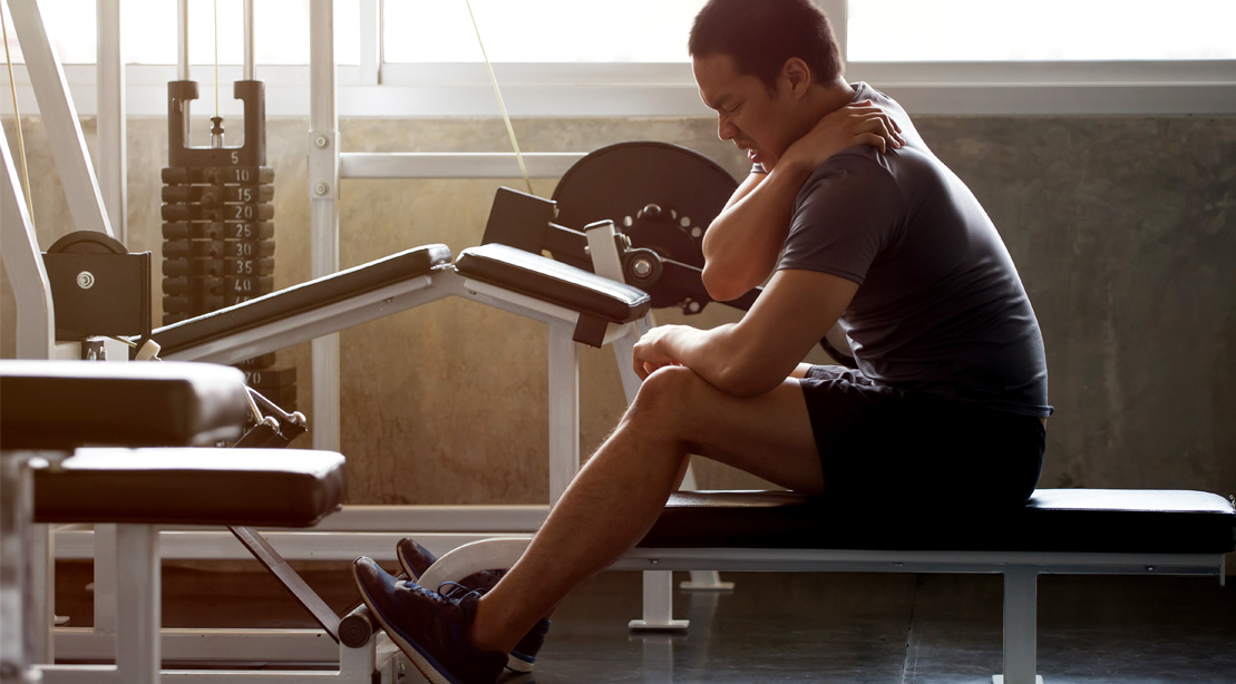 Young male working out in the gym with a shoulder injury and recovering with the muscle flossing technique