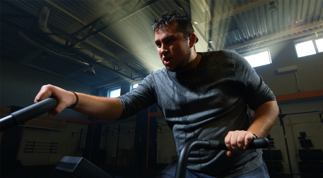 Overweight male sweating and exercising on a stationary bike