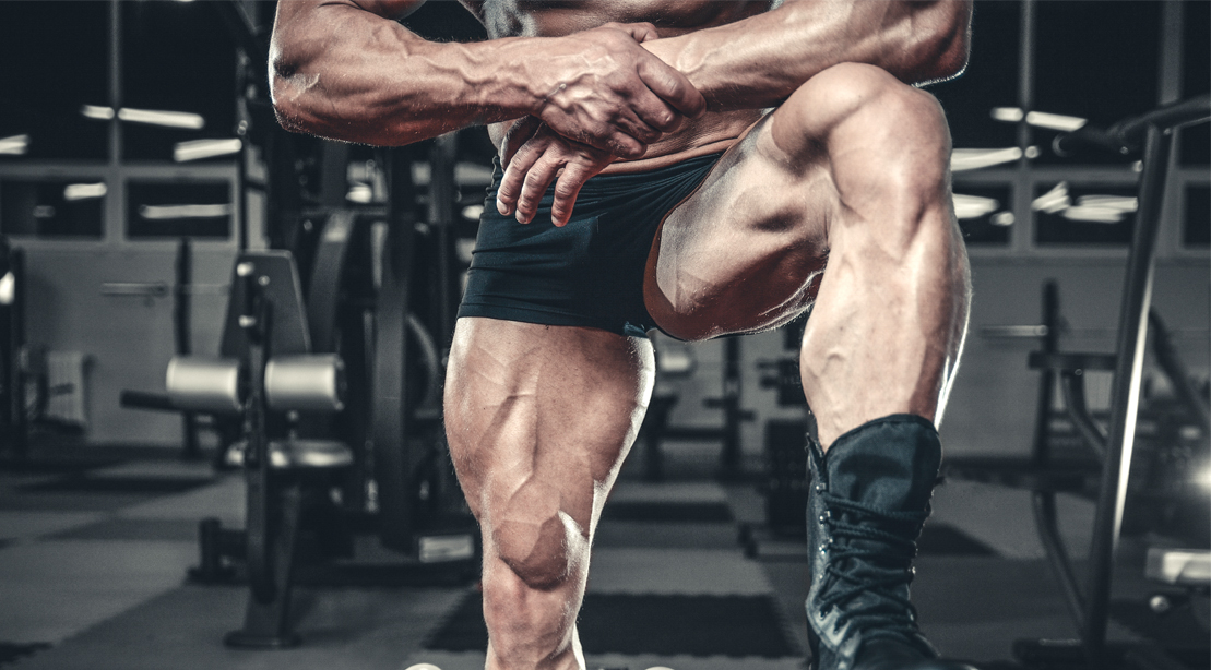 Bodybuilder with big quad muscles on a bench