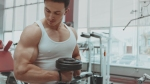 Man Doing Biceps Curls in the Gym Focusing