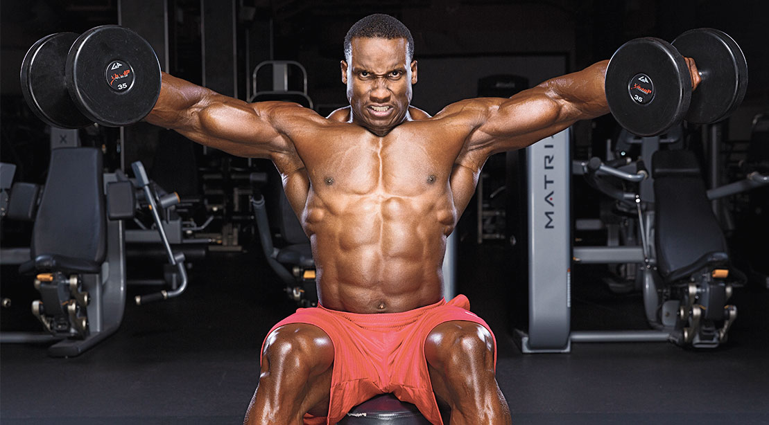 Bodybuilder doing a shoulder workout with a seated dumbbell lateral raise exercise