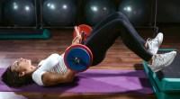 Female doing barbell glue bridge in a gym