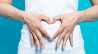 Fingers shaped in the form of a heart placed over persons gut