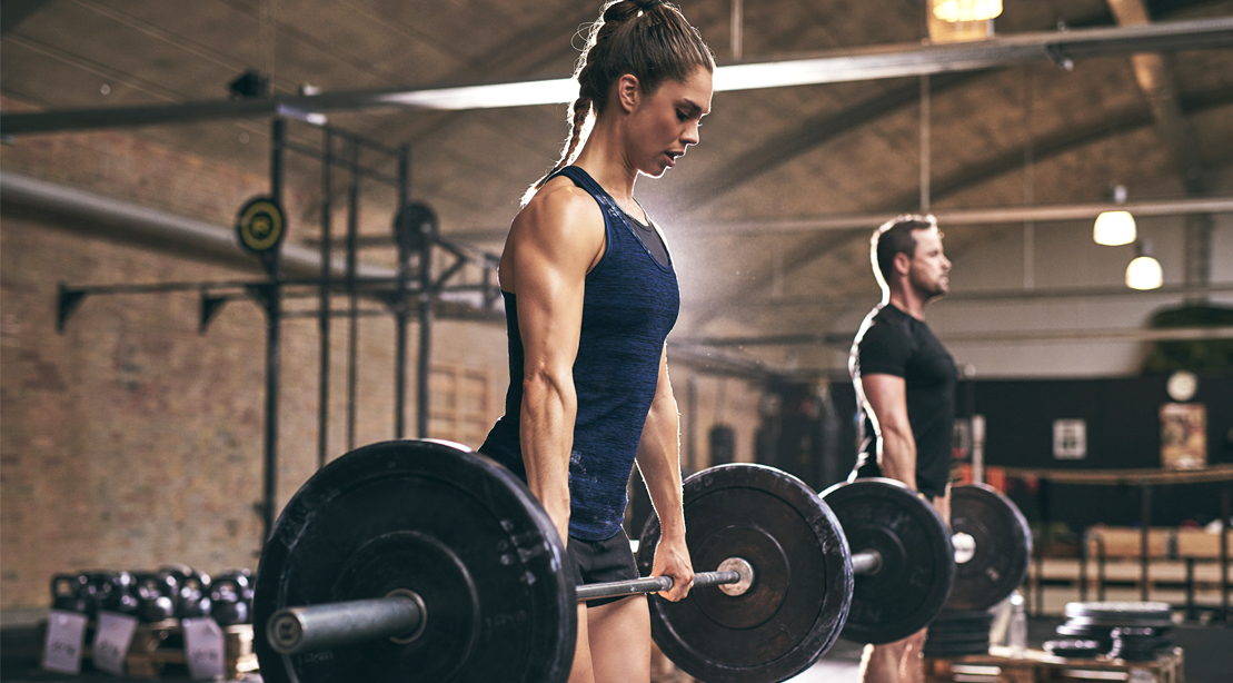 Fit couple working out in the gym with a barbell deadlift exercise in a barbell complex