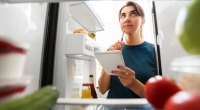 Girl-With-Notebook-Thinking-About-Food-In-Fridge