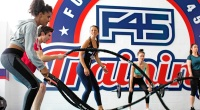 Females working out in a group fitness class doing battle ropes exercise for F45