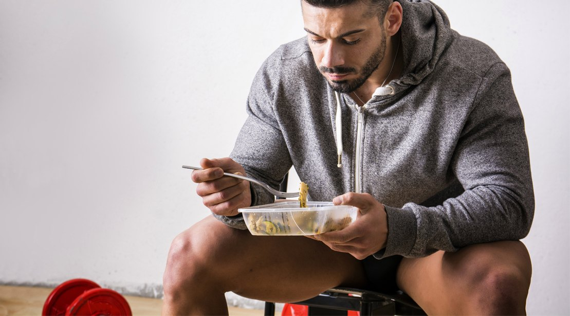 Man dieting eating a pre-workout meal or post-workout meal prepped meal from a tupperware in the gym