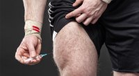 Man injecting his quads with anabolic steroids with a syringe needle