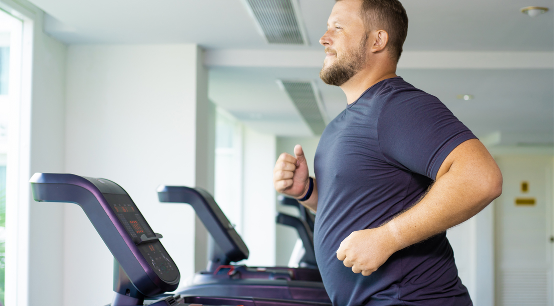 Overweight man running on a treadmill in an empty gym