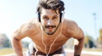 Physically fit man wearing headphones while doing outdoor exercises