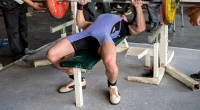 Bench-Presser-Lifting-Barbell-Feet-Behind-The-Knee