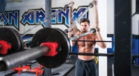 Muscular male model demonstrating how to do a viking press exercise