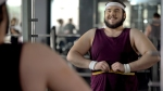 Happy and overweight man measuring his stomach in the gym mirror