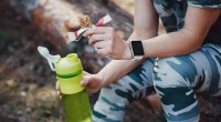 Fitness-Person-Sitting-On-Log-Holding-Eaten-Protein-Bar-And-Water-Bottle