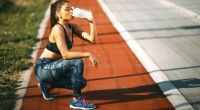Girl-Kneeling-Down-Drinking-Protein-Shake-on-Track