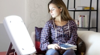 Girl-On-Couch-Holding-Book-Using-Light-Therapy