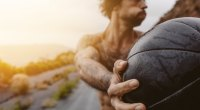 Guy-Holding-Medicine-Ball-Sunset-On-The Road
