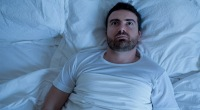 A man lying in bed with his eyes open trying to fall asleep