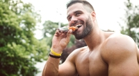 Happy bodybuilder eating a protein bar outdoors