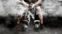 Kettlebells in front of bodybuilder creating a cloud of chaulk by clapping his hands