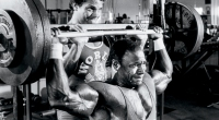 Lee Haney doing a behind the neck press exercise with a spotter