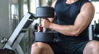 Muscular man with biceps holding a heavy dumbbell sitting on his knee