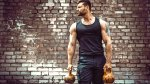 Man-In-Front-Of-Brick-Wall-Holding-Kettlebell