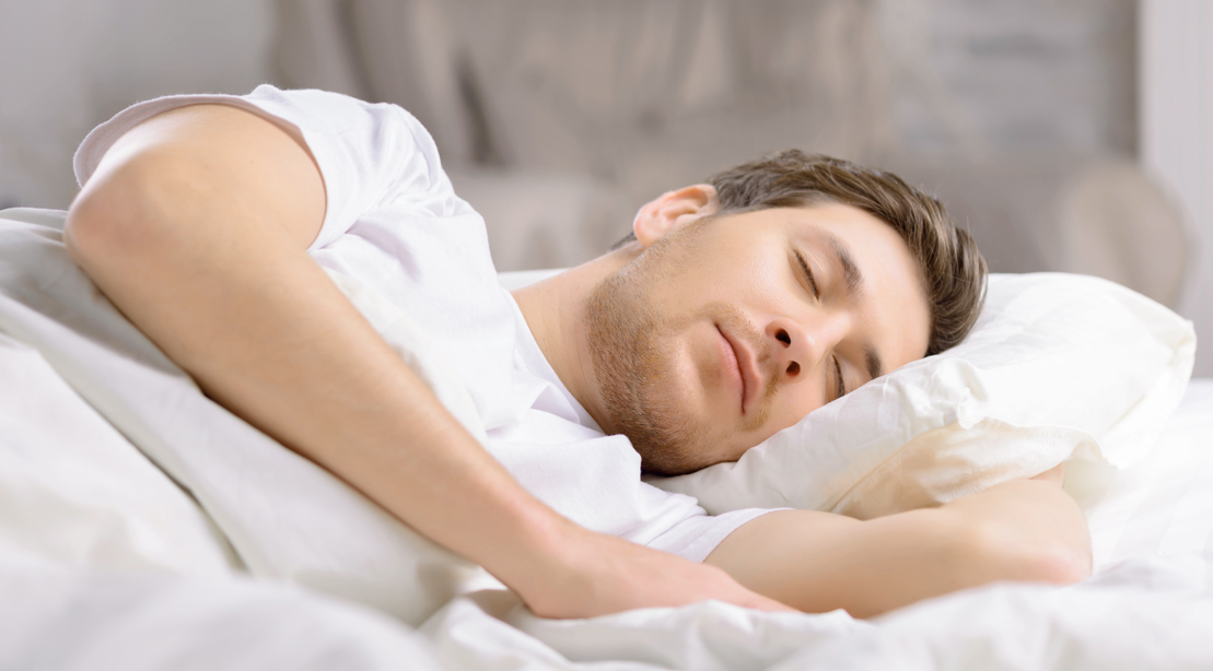Man sleeping peacefully in a bed with white sheets.